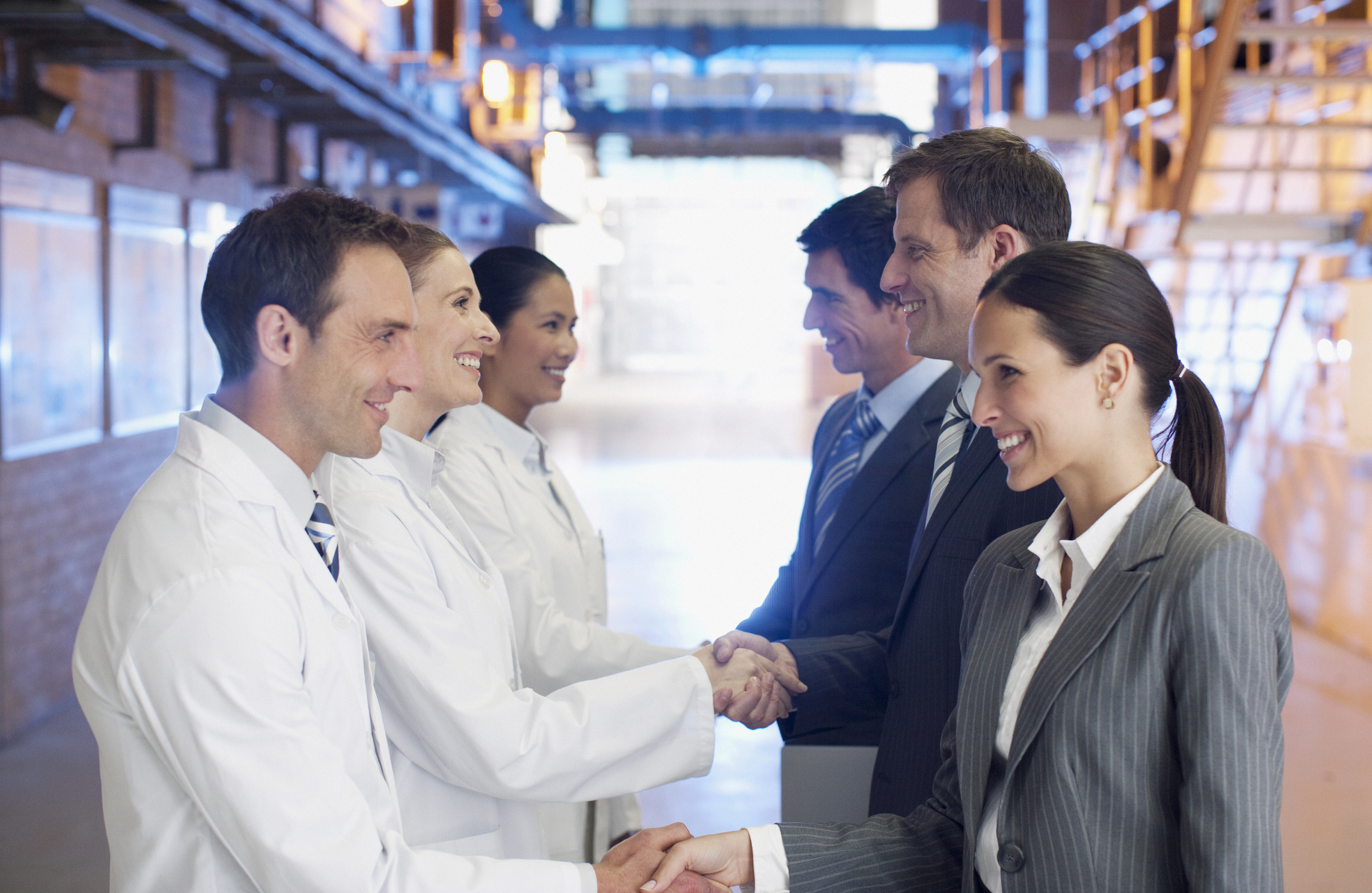 Image of Scientists shaking hands with Business men & women