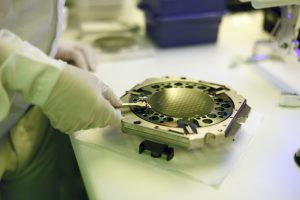 Lab technician examining a silicon wafer in a clean room.