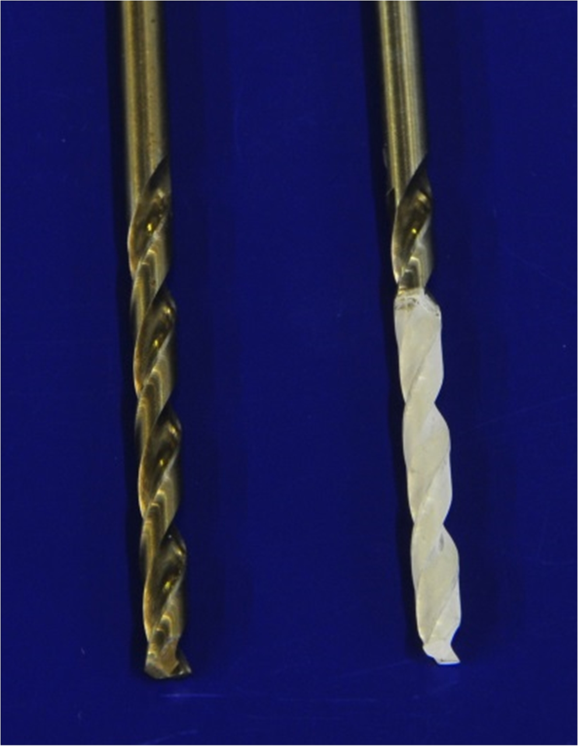 Photo of two drill bits on a dark blue background, one has a white coating on the bottom half